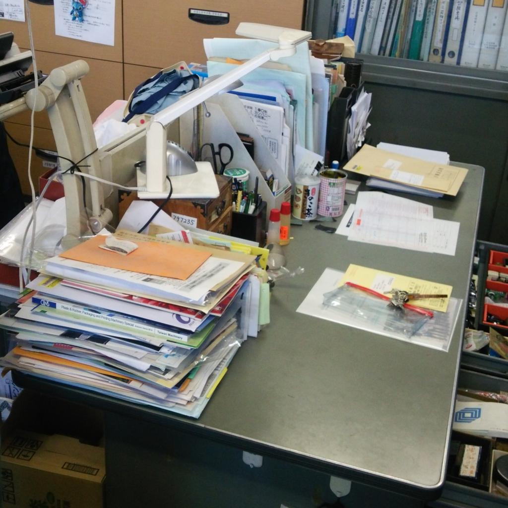書類山積みのデスク